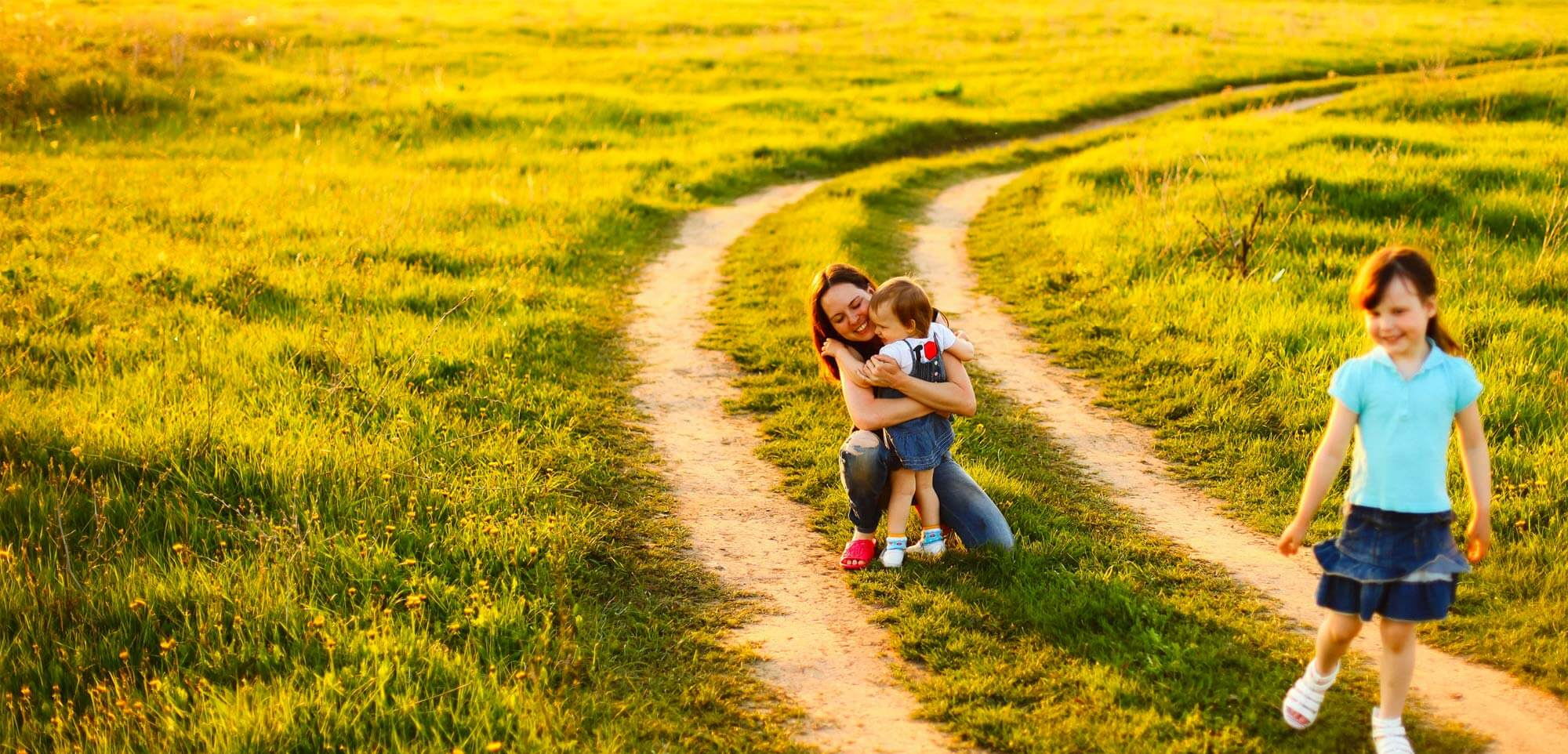 Mom hugging baby on dirt road.