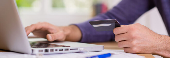 Person holding debit or credit card and using computer.